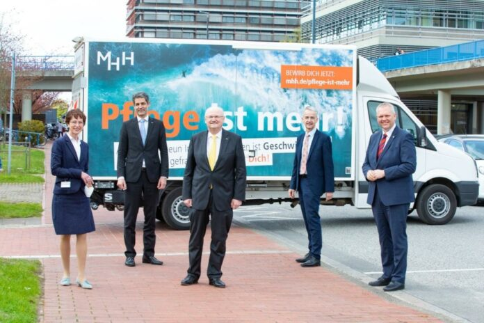 Martina Saurin, Andreas Fischer, Professor Dr. Michael Manns, Professor Dr. Frank Lammert und Minister Björn Thümler vor einem Plakat der MHH-Pflegekampagne.