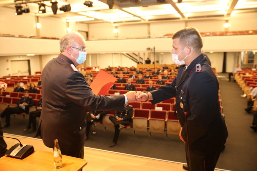 Stellv. Stadtbrandmeister Thomas Ajrumow beglückwünscht Sascha Küsterbeck mittels Corona-Gruss